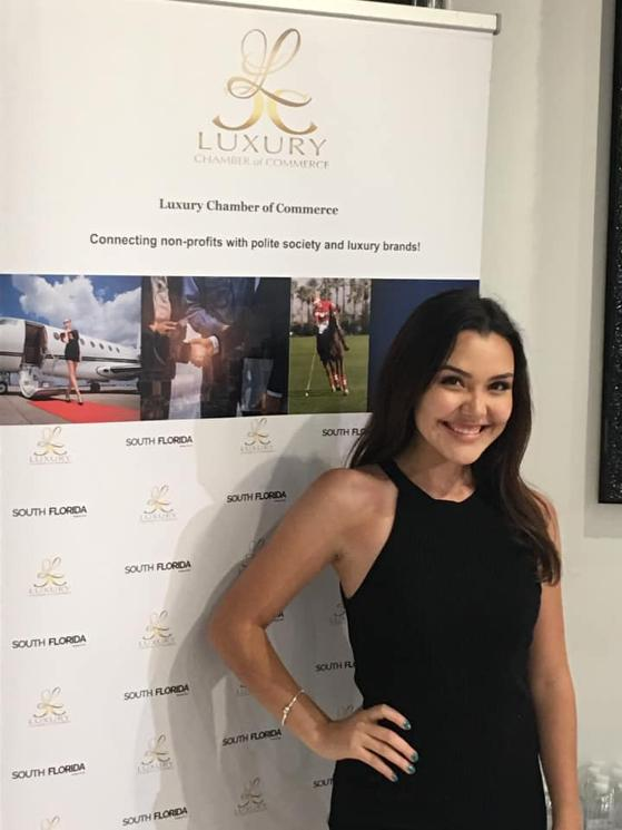 Celine Alva in front of Luxury Chamber Step and Repeat or Tradeshow Banner June 2020