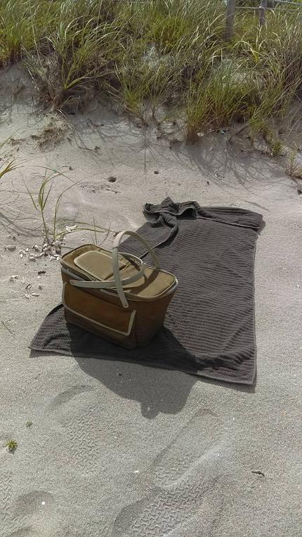 foosteeps in the sand, towel and picnic basket on florida beach