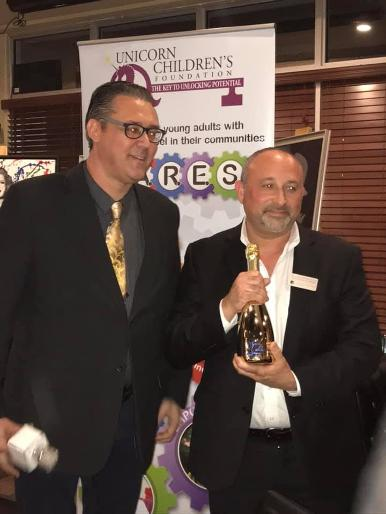 Jay Shapiro and door prize winner William Gerstein wins a bottle of Lamborgini Champagne at a Luxury Chamber of Commerce and Unicorn Childrens Foundation Networking Event, Temper Grille in Boca Raton, FL